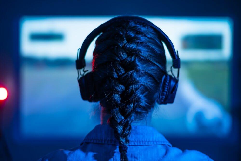 Girl wearing headphones while sim racing